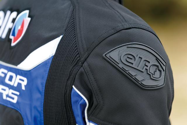 画像: 肩にはラバー素材のロゴプレートが。肩や腕の白いラインがリフレクターとしても機能している。二の腕部分には余計なバタつきを抑えるアジャストベルトを装備。