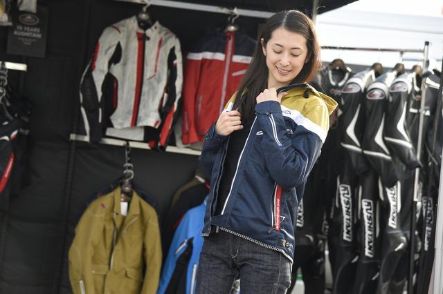 画像: この日、レーシングスーツのレンタルや、持ち込みレーシングスーツの補修、新製品の紹介などで大忙しだったクシタニ・ブース。春夏物のジャケットを試着することもできたので、気に入った商品をとりあえず試着中の朱香。「アウトドアっぽくて、イイですよねぇ」とのこと。