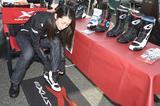 画像: 山城ブースではEXUSTAR(エグザスター)のブーツを多数展示! ツーリングブーツからレーシングブーツまで幅広くラインアップしている。ブーツ自体は日本人の足型に合わせた作りとなっており、試着サービスも人気となっていました。というわけで、朱香試し履きの様子。 www.kkyamasiro.co.jp