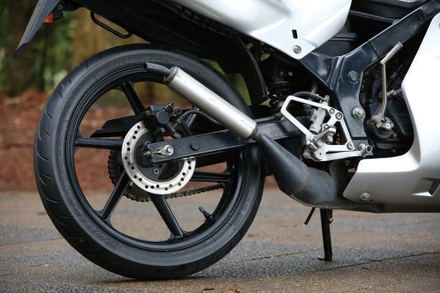 画像: リアがディスクブレーキなのもNS50Fとは違う部分。6本スポークのデザインはホンダスポーツバイク共通のデザイン。サイレンサーが黒じゃなくアルミ風なのは後期型の特徴である。