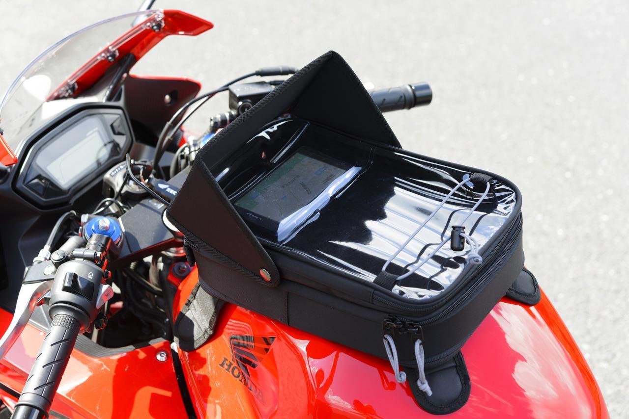 画像: HenlyBegins スマホタンクバッグ 価格:Mサイズ・1万円/Lサイズ・1万1500円(共に税別価格) 真夏の直射日光下でもバイザーがあることで画面はクッキリ見える。スマホの下にはツーリングマップルも入れられ、停車時にグローブ部などを挟み込めるドローコードも備えている。
