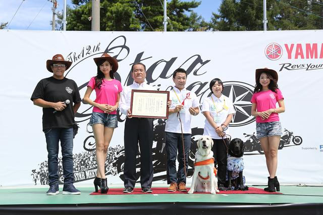 画像: 1989年にスタートしたヤマハナイスライド募金の贈呈式。「私たちに バイクがあるように、目の不自由な方に盲導犬を」という呼びかけのもと、日本盲導犬協会へ盲導犬の育成資金を贈ることを目的としている募金制度です。