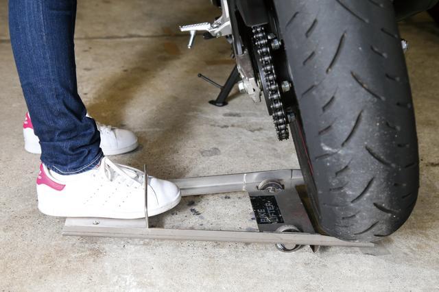 画像: タイヤの下にバイクリフターを滑り込ませ、あとは踏み込めばリアタイヤが浮いた状態になる。その状態でバイクを押せば、簡単にタイヤ位置をスライドさせることができるのだ。