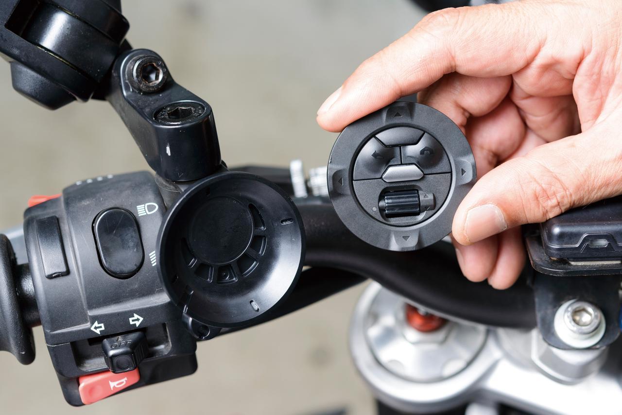 画像: ミラー基部に挟み込んだステーに両面テープでホルダーを固定し、コントローラーはマグネットで装着。オートバイから離れる時は外して持ち歩けばいい。