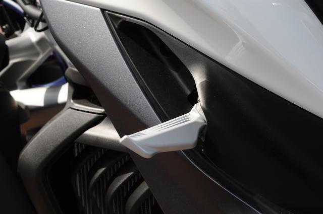 画像: 現行モデル同様のワンタッチでオープンするタイプの折りたたみ式タンデムステップを装備する。