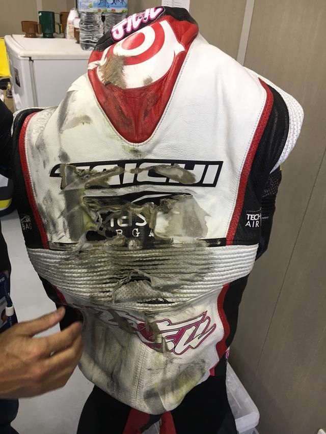画像: こちらは前戦のアラゴンGPでクラッシュした、Teluru SAG Teamの長島哲太選手のレーシングスーツ。これだけ大きなダメージを受けると、即座のリペアは難しいですが、シャーリング部分や背中部分など、部分ごとのアッセンブリー修理が可能だそうです。