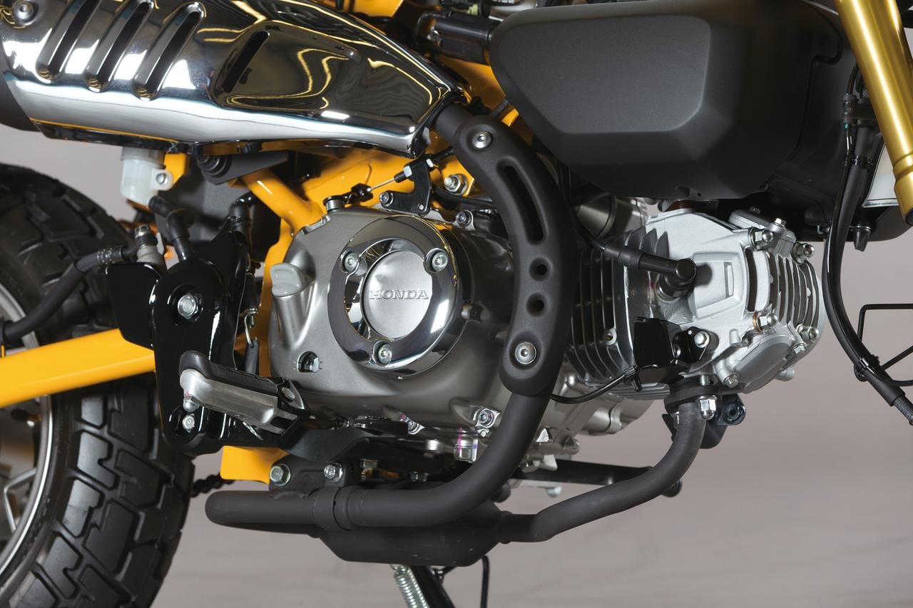 画像: グロム譲りのSOHC単気筒はボア52.4×ストローク57.9㎜で、排気量は124㏄。クランクケースにはステップにのせた足が当たらぬようメッキのリングガードをセットした。