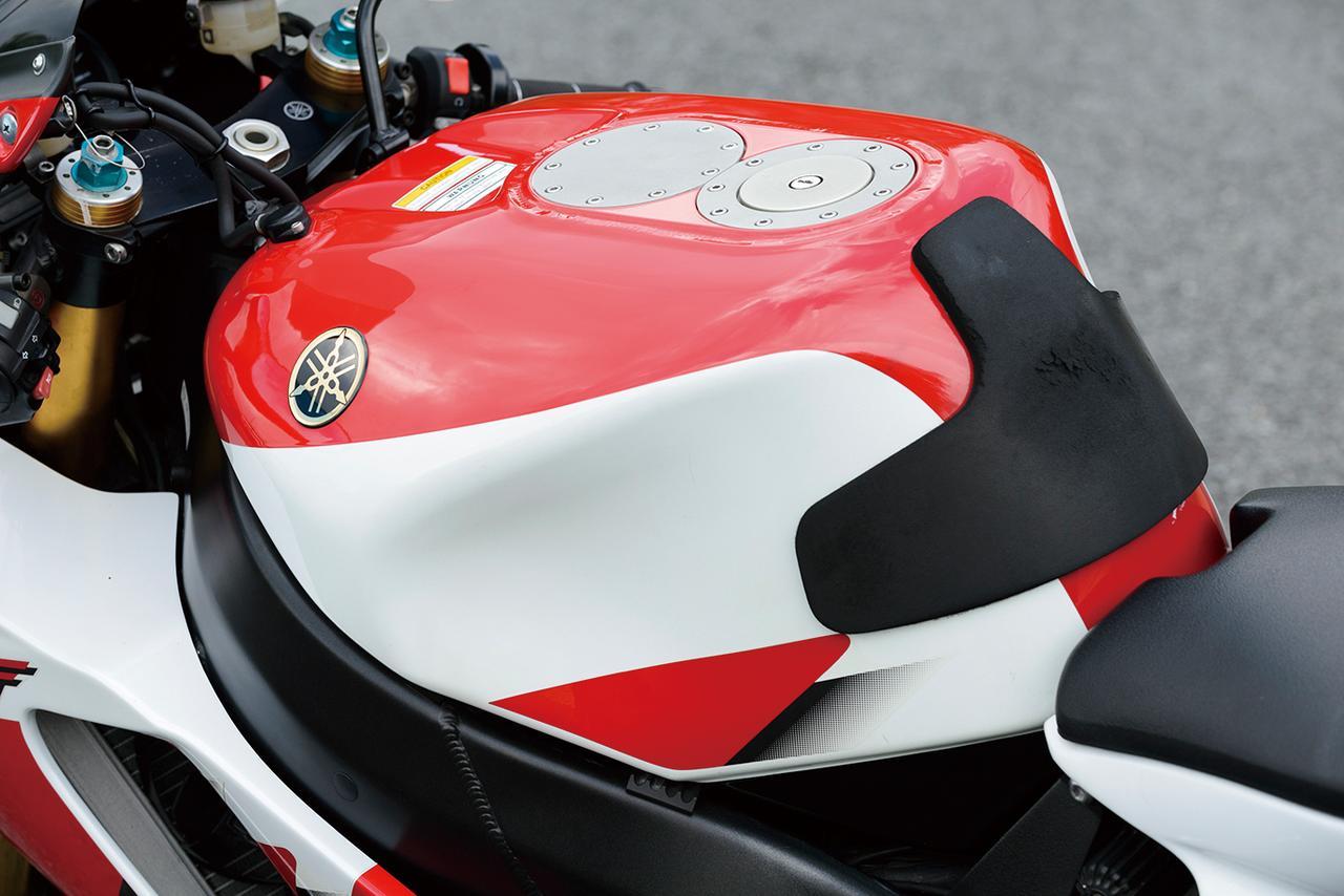画像: 軽量なアルミ製燃料タンクは耐久レース出場を見据えて23Lという大容量。タンク上面にはクイックチャージャーの受け口用スペースまで確保されている。タンク幅は広めだが、ヒジでホールドしやすいというメリットもある。