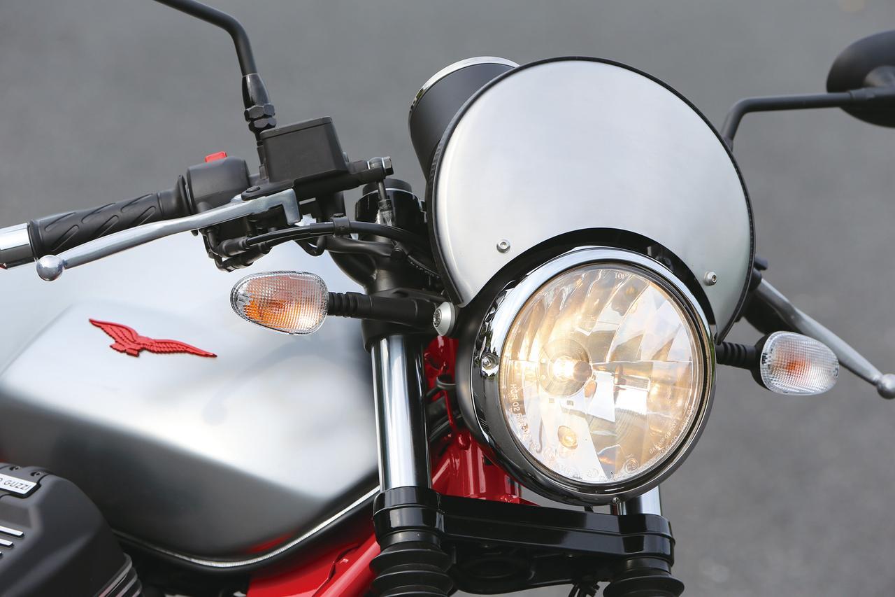 画像: ヘッドライト上に備わる、特徴的なゼッケンプレート風のメーターバイザーがレーサーの特徴。今回から素材がブラシ仕上げのアルミニウム製に変更された。