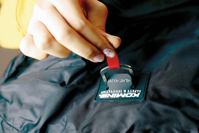 画像: バッグのスリットに顎紐のDリングを通してからヘルメットホルダーに留めるので、風で飛ばされることもない。