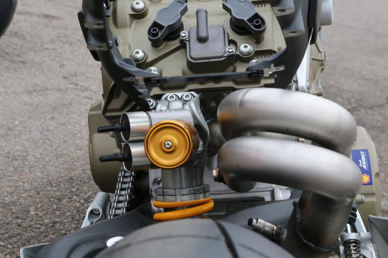 画像: 後ろシリンダーのエキパイはリアサスペンションを避けるためにシリンダーヘッドから出た直後に縦方向に捻られ、そのままクランクケース下の膨張室に連結されている。