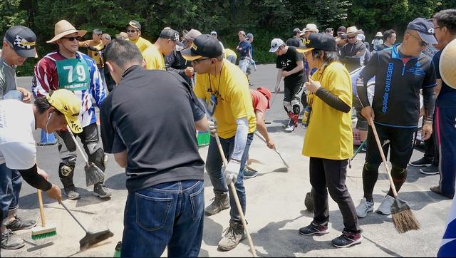 画像: オフィシャルや運営スタッフだけでなく、選手たちまで総出で手に手にブラシやホウキを持ってオイルを処理!
