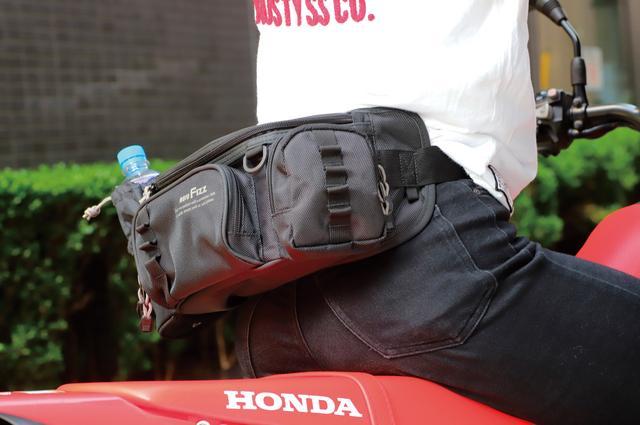 画像: 素材は頑丈な1680Dナイロン。生地自体が厚手なので型崩れもしにくい。ポケットに付いてる波状のベルトはカラビナを通すためのループ。