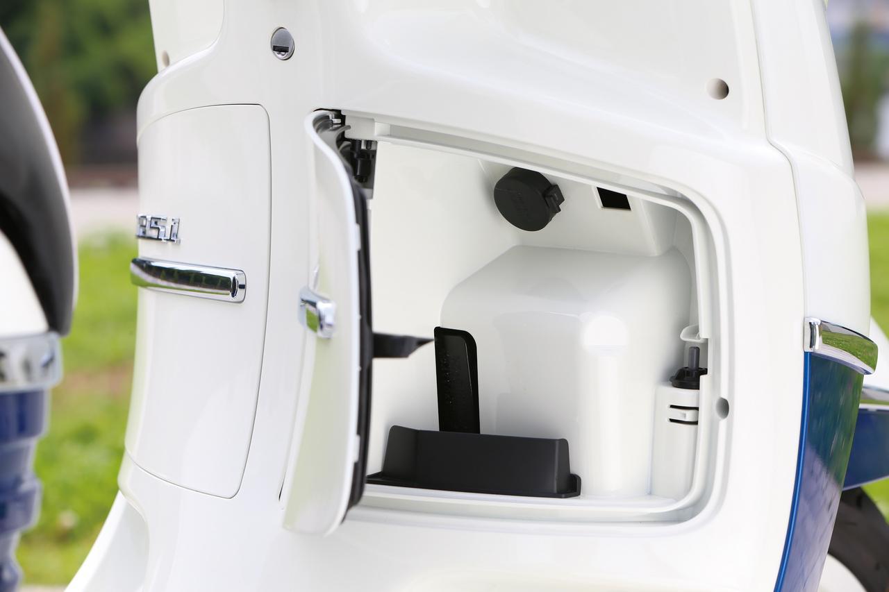 画像: フロアボード前方に2カ所のドアを設置。左側が給油口、右側は小物を収納できるグローブボックスで内部に12Vの電源ソケットも用意されている。