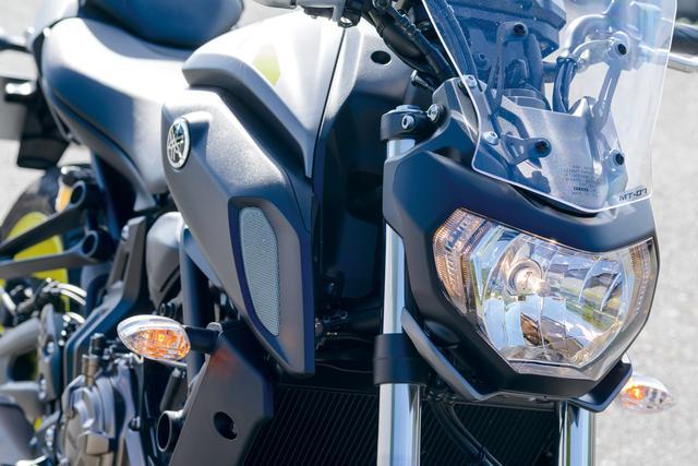 画像: 初代MT-07よりも大型化されたヘッドライトで、MTシリーズらしいコンパクト感とアジリティ感を強調。下部の左右には小さなウイングレットが装着されている。