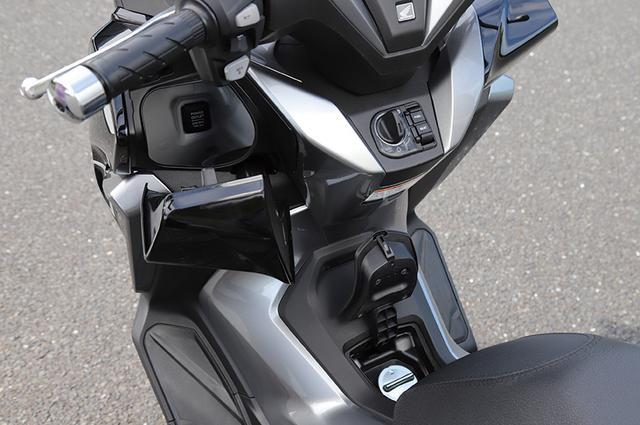 画像: フロントポケットはプッシュ開閉式の左側のみ。内部には12Vソケットが用意される。給油口はスイッチ脇のボタンで開ける。