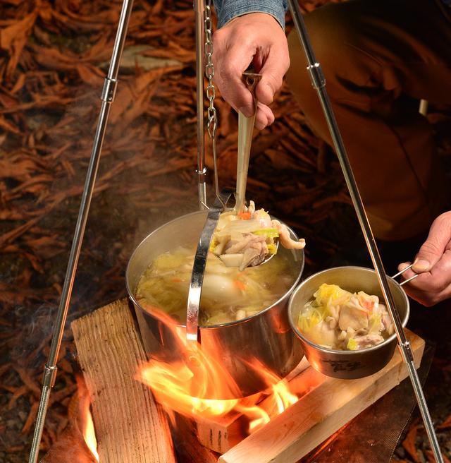 画像: トライポッドと焚き火台を組み合わせて作った、もつ鍋。吊るした鍋から直接取り分ける際は、お玉を持つ手などがトライポッドの脚に触れないように注意。やけどや倒壊の恐れがあります。