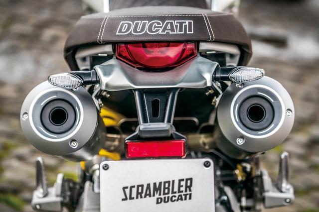 画像: 今回スクランブラー1100だけの特徴である二本出しステンレスマフラー。シートのすぐ下に配置され、ビジュアル的にもリアの大きな特徴ともなっている。