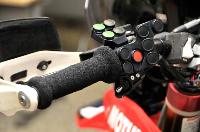 画像: ラリーマシンのグリップは、サンドライディングに最適化されたスポンジグリップが定番。コマ図ロールマップやラリーコンピューターを動かすための各種スイッチ類が備わる。