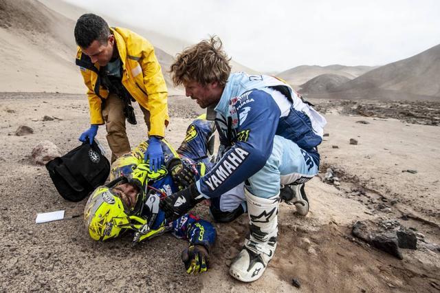 画像: 転倒して負傷した#63シェルコのライダーLorenzo Santolinoを救済するA.ファン・ビファレン(ヤマハ)。ダカールラリーではライバル同士でも助け合いが行なわれ、フェアプレイでタイムロスしたライダーにはタイムが加算されないように救済措置がとられます。