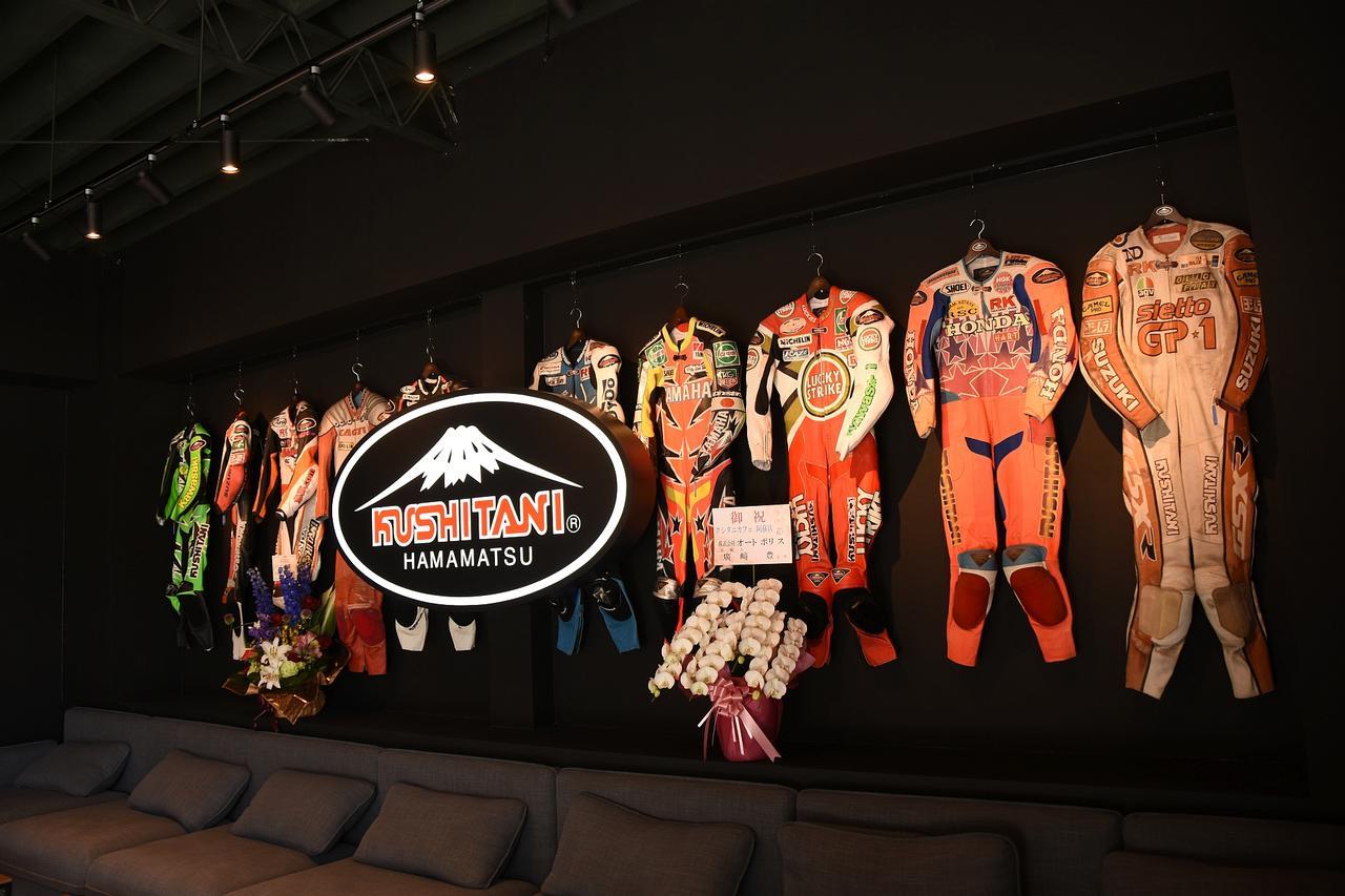 画像: カフェの壁一面に歴代のライダーのレーシングスーツが飾ってあります