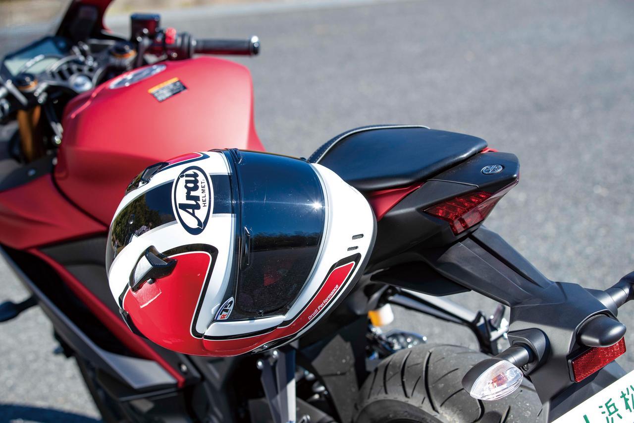 画像: ヘルメットホルダーは持たないが、タンデムシート裏のフックを利用すればヘルメットをこのように固定しておくことが可能。