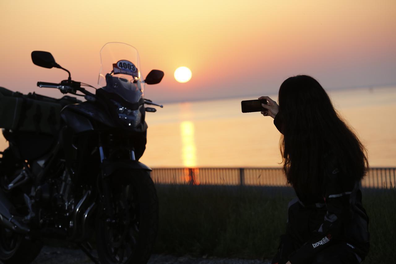 画像: SSTRのレギュレーションとして、バイクに貼られたゼッケンと朝日が見えるようにスマートフォンなどで撮影します。