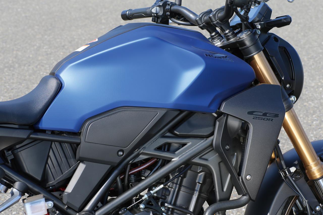 画像: 新世代CB-Rシリーズ共通のイメージでまとめられた、立体感あふれる造形の燃料タンク。新色ではシュラウドがブラックアウトされ、精悍な雰囲気に一変。