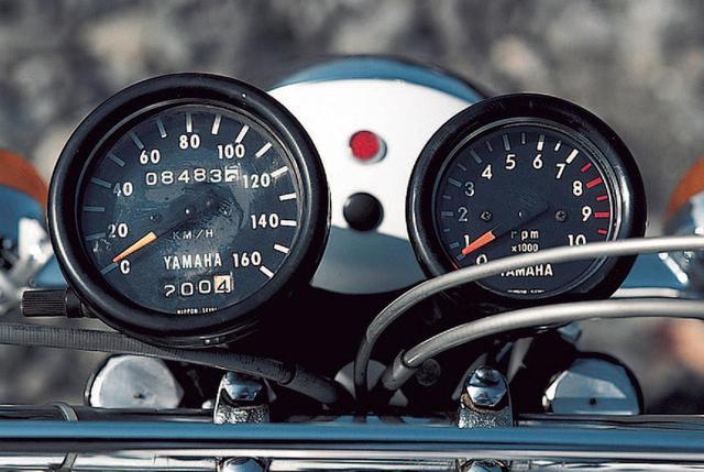画像: メーターは2連式で、左が160㎞/hを上限とする速度計、右が10000rpmスケールで、7500rpmからレッドゾーンが始まる回転計。燃料タンクと同様に白く塗られたヘッドライトケースの上にある赤丸はハイビームのインジケーターランプ。警告灯はこれ以外に存在せず。速度計の文字盤にオド/トリップメーターがある。