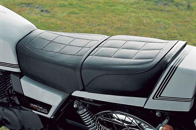 画像: シートは前後に長くフラットな形状で、タンデム部の下側には燃料タンクなどと同色の樹脂パーツを取り付けている。メインキーのロック解除で横向きに開く構造で、テールカウルの内側を小物入れとして活用している。