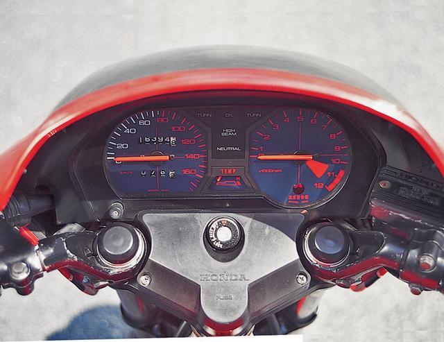 画像: トップブリッジ上面をヒューズボックスとして活用するのはVT250Fと同じで、HONDAのロゴがあるカバーを外すとブレードヒューズが並んでいる。2連式のメーターはVT250Fとほぼ同デザインで、左の速度計は160㎞/hスケールで80㎞/h以上の文字と目盛りを赤とする。すべてを赤で記した右側の回転計は電気式で、12000rpmが上限、10500rpmより上をレッドゾーンとする。両者に挟まれる警告灯は、最上段が左右ウィンカーとオイルプレッシャー。その下部にハイビームとニュートラルが並び、下段には赤い針を持つ水温計を置く。ビキニカウル上部に四角い大穴を設けてスモークのスクリーンを装着するため、乗車時に円弧状に見えるのはスクリーンではなくカウルの端部だ。