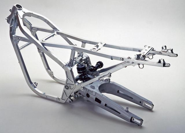 画像: NS250Rが使うフレームとスイングアームで、フレームの基本的な構造はRS250Rと共通。ホンダの公道向け市販車でアルミフレームを使うモデルはNS250Rが最初だった。ヘッドパイプ周辺とスイングアームピボットを持つ左右プレートは鋳造製で、タンク/アンダーチューブやシートレールなどには角断面パイプを使用。フレーム単体重量は10㎏弱で、Fのスチール製に比べて約3㎏軽量と発表された。専用設計のスイングアームは、左右レールをテーパー状として肉抜き孔を与えた独特な外観だ。