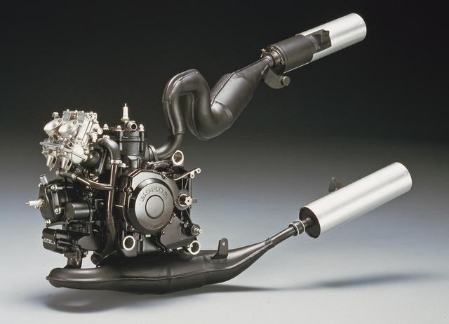 画像: 水冷ピストンリードバルブ90度V型2気筒は、基本はRS250Rと共通、同一のクランクケースを使う。56×50.6㎜のボア×ストロークより249.3㏄を得ており、最高出力:45ps/9500rpm、最大トルク:3.6㎏-m/8500rpmを発揮(MVX250Fに対し、5ps、0.4㎏-mずつ増大)。2基となったキャブはMVXと同様にスクエアバルブを装備してボディを小型化。後方シリンダー用のチャンバーは、充分な管長を確保しつつシートカウル内に収めるため、大きく湾曲している。
