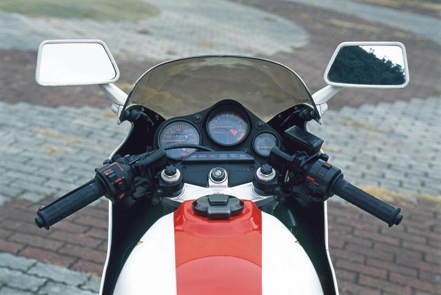 画像: 黒仕上げのセパレートハンドルはトップブリッジ上方でフロントフォークをクランプ。ハンドルの垂れ角が大きくないことから上半身の前傾は強くない。左右スイッチはMVX250Fと同様に赤で文字を記す。正立式フロントフォークは、当時としては太いφ37㎜のインナーチューブを使用。エアアシスト式で、上端部に見える黒い樹脂キャップの下にエアバルブを配する。調整機構は持たない。