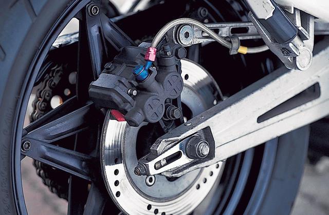 画像: リアブレーキは、φ220㎜ソリッドディスクと片押し式2ピストンキャリパーの組み合わせ。撮影車のブレーキホースはステンレスメッシュに交換されているが、STDは黒いゴムホースを使用する。スイングアームはRS250Rとは別物、専用設計品だ。