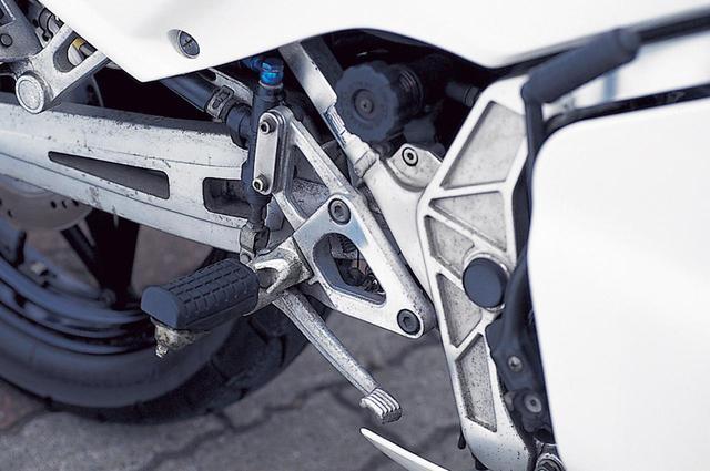画像: 小型のアルミ製ブラケットをボルト2本でフレームに固定し、大型の滑り止めラバーを持つ左右フットペグや、ブレーキペダルおよびマスターシリンダーを支持。
