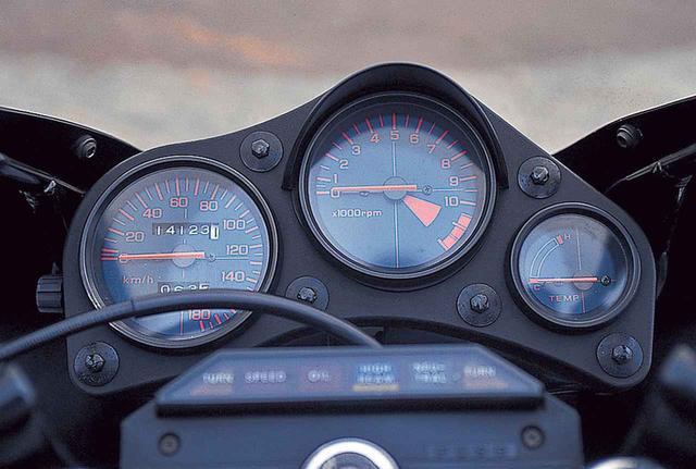 画像: メーターは3連で、左が180㎞/hスケールの速度計、視認性を高めるためのバイザーを備える中央の回転計は12000rpmが上限で10500rpmからをレッドゾーンとする。右端は水温計で、各メーターとも文字盤は濃紺、数字や目盛り、針などは赤とされる。インジケーターランプはメーター手前に横方向に整列し、左から、左ウィンカー、速度警告灯、オイルプレッシャー、ハイビーム、ニュートラル、右ウィンカー。
