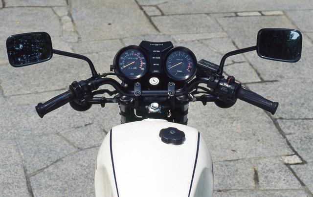 画像: ハンドルは黒仕上げのパイプを使ったセミアップだが、グリップ位置は低くセパレートのように上半身が前傾する乗車姿勢となった。左右レバーやトップブリッジ、バックミラー、ウィンカーのボディやステーなど多くの部分をブラックで統一する。