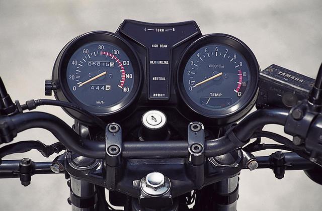 画像: メーターは丸形の2連タイプで、左が160㎞/hを上限とする速度計、右が12000rpmスケールで、9500rpmからレッドゾーンが始まる回転計。中央部にインジケーターランプが並び、最上段は左右ウィンカー、その下がハイビーム。2ストオイル残量警告灯、尾灯電球切れ告知ランプ、ニュートラル、速度警告灯を配置。タコメーターの文字盤の下部には水温計を内蔵する。