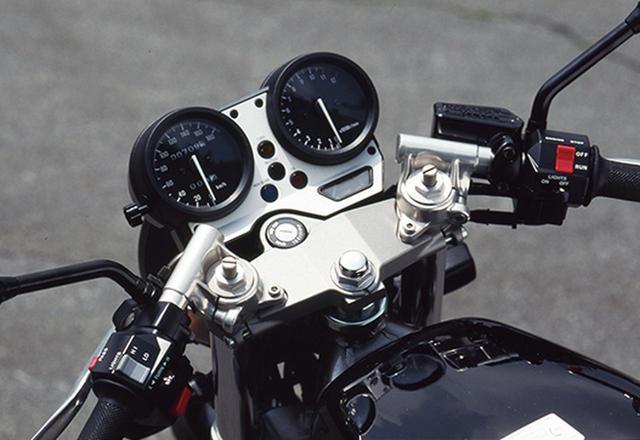 画像: メーターは左に速度計、右に回転計を配する2連タイプで、これらを支持するアルミプレートに各種の警告灯を並べる。ハンドルはアルミのセパレートで、クランプ部はトップブリッジ上方にあるので乗車時に上半身が前傾する度合いは強くはない。