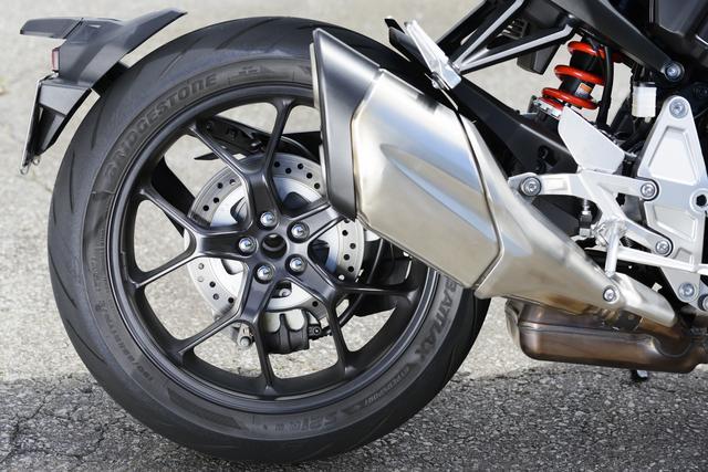 画像: 排気効率向上と深いバンク角を両立したマフラー。片持ちスイングアームに装着されるリアホイールはCB1000R専用に設計されたものだ。