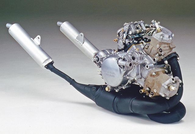 画像: 初代NSR250Rが搭載する水冷2サイクル90度V型2気筒、型式名MC16Eである。MVX250Fが積んだMC09E、NS250R/F用となるMC11Eなどはピストンリードバルブだが、MC16Eではクランクケースリードバルブに変更しており、キャブレターは前後気筒の間ではなくリアシリンダー後方に置かれる。ホンダがこのクラスのレーサーでVツインを選んだのは、横幅が狭いので前面投影面積が減って空力特性に優れるうえにバンク角を稼げる、前側気筒を前傾させることで低重心化、前輪分布荷重を増やせるなどの理由からだ。MC16Eは、同一のボア×ストロークで並列2気筒とした場合より横幅を約50㎜削減しており、前側気筒を水平から20度前傾させてエンジンを搭載、理想的な前後重量配分を得ているという。キャブが後ろ側にあるため2本のチャンバーは前側に向かって伸び、大きく湾曲してクランクケース下に潜り込む。左右のサイレンサーは総アルミ製で、チャンバーにボルト留めされるフロントプレートとそれに続く外筒を一体成型、後端に湾曲した細いパイプを与えており、外観だけでなく軽量という機能面でもレーサーのそれを踏襲している。