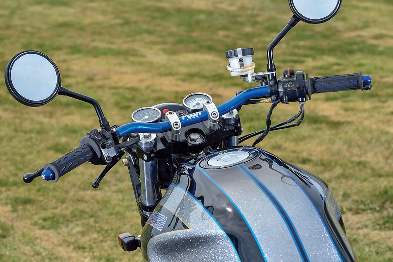画像: ハンドルバーはポッシュ製で、車体色変更に合わせてブルーに変更する。バーエンド、グリップも同様。メーターも一般的な2眼式から小径なものに換装してフラットな配置に変えている。左スイッチボックス下に見えるレバーはSRならではのキックスタートのデコンプ用だ。