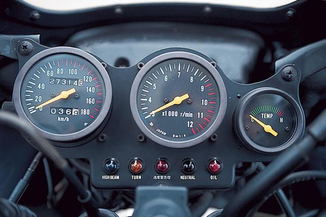 画像: プレートに埋め込まれたメーターはレーサーを思わせるデザインで、12000rpmスケールで3000rpmを起点とするタコメーターを中央に配置する。左は80~180㎞/hの目盛りを赤としたスピードメーター、右は水温計だ。下側には各種インジケーターランプが並び、左から、ハイビーム、ウィンカー、速度警告灯、ニュートラル、オイルプレッシャーとなる。