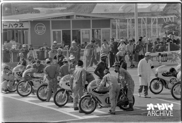 画像: 1964年日本GP・250ccクラス、スタート直前のグリッド。ポールを取ったジム・レッドマンのホンダRC165の向こうで、予選2位・ゼッケン22のヤマハRD56に乗るフィル・リードとレッドマンが言葉を交わしている。ゼッケン28のMZの右手にマイク・ヘイルウッドの姿があり、一番向こうで腕を組むのは2台目のRC165を駆る125ccチャンピオンのルイジ・タベリ。2列目手前、ゼッケン11のRD56のライダーは伊藤史朗。台数は少ないが豪華なメンバーだ。