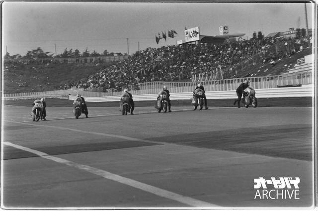 画像: 1964年日本GP・350ccクラス、決勝スタートのまさにその瞬間! 確かに6台しかいない…。当時は押しがけスタートで、ポールポジションのゼッケン10、レッドマンがいち早く駆け出している。一番左のゼッケン23がチェチェップ。