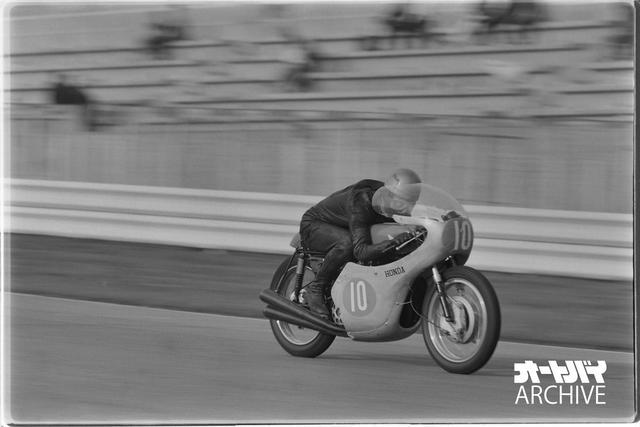 画像: 鈴鹿のホームストレートを駆け抜けるレッドマンとRC172。レッドマンは当時ホンダの絶対的エースで、1961〜1966年にかけて125ccから500ccまで幅広く出場。世界GP通算45勝、350ccクラスでの1962〜1965年の4連覇を含む6つのタイトルを獲得。1964年ダッチTTでは出場3クラス全て優勝など、圧倒的な速さを誇った。