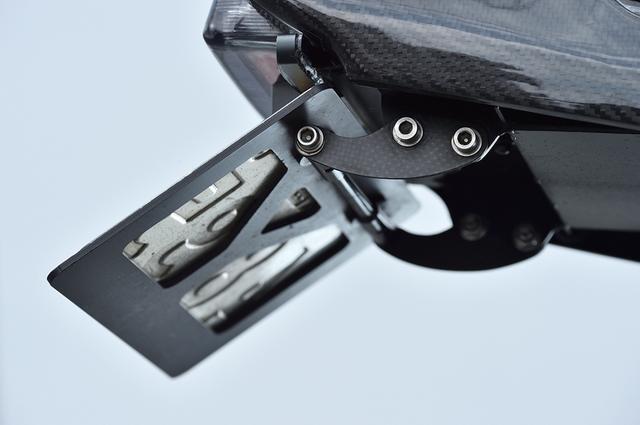画像: サブフレームから伸びるナンバーステーもドライカーボン製だ。ナンバープレート上に小ぶりなリアウインカー、その上にテールライト。