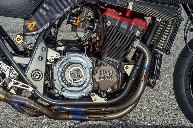 画像: エンジンは早い段階で'91GSX-R1100油冷に換装されていた。ポート加工とヨシムラST-1カム組み込みなどで150psを発揮、この換装でも軽量化が行われた。クラッチカバーはスケルトンタイプ。キャブはTMR-MJNブラックアブソリュート/デュアルスタックを装着する。
