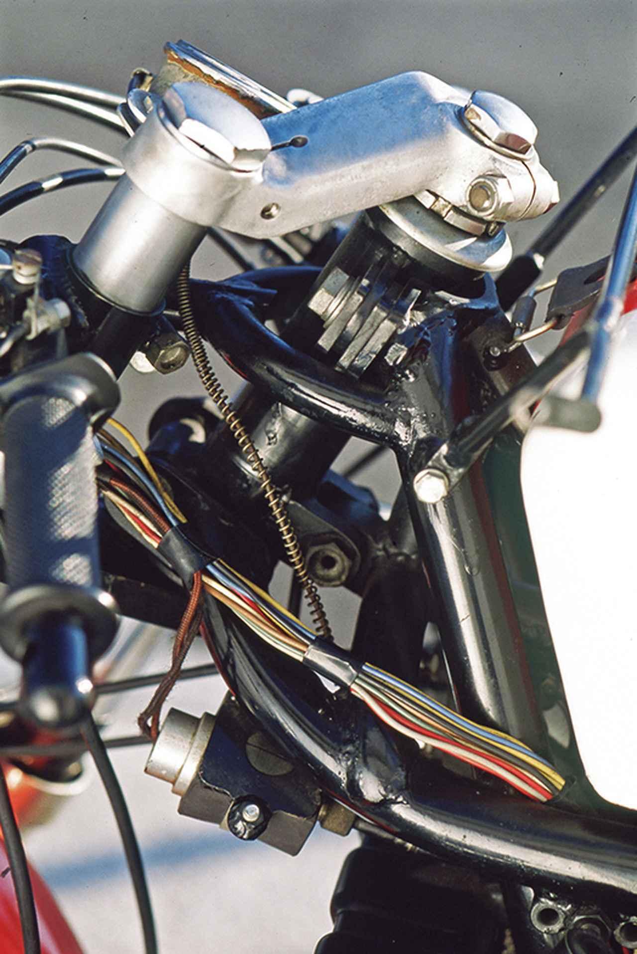 画像: フロントフォークは異様に細く、ステアリングヘッドまわりは華奢に見える。ヘッドパイプ~フレーム間のプレートの交換で、キャスター角を変更できる機構を持つ。